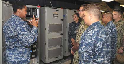 NEWPORT NEWS, Va. (Aug. 21, 2018) Information Systems Technician 2nd Class Jacqueline Francis (left), from New York, assigned to USS Gerald R. Ford's (CVN 78) combat systems department, trains USS George Washington (CVN 73) Sailors on how to use the Consolidated Afloat Network Enterprise System. (U.S. Navy photo by Mass Communication Specialist 3rd Class Liz Thompson) (This image has been altered by blurring out badges for security purposes)